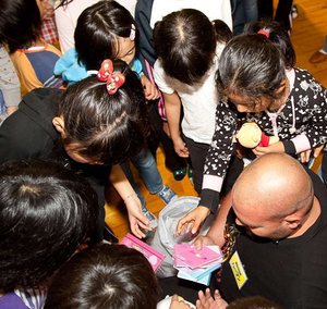 A Topcon employee from the U.S. (bottom right) is shown providing gifts to children in an orphanage near Tokyo as part of the social volunteerism component of the TOGETHER project