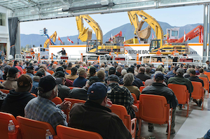 A view from the back of a Ritchie Bros. auction theater in Chilliwack, B.C., Canada. Most mobile equipment is driven over a ramp in front of a crowd of bidders