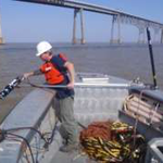 Engineer deploying sonar from side of boat