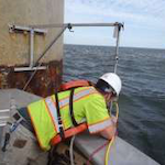 Engineer deploying sonar head attached to bracket system on pier