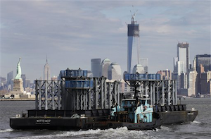 The spire of One World Trade Center approaches New York Harbor with the New York skyline in the background. (AP Photo/Mark Lennihan)