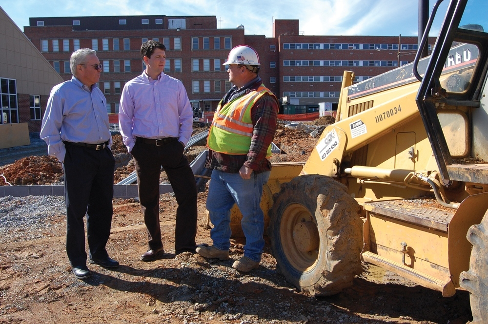 Mitch Cox (left) discusses a sitework with Raymond McBride, president of Mitch Cox Construction and Scotty Lane, senior superintendent.