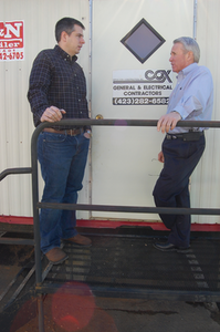 Project manager Odell Cash (left) and Mitch Cox confer on the progress of a commercial building project.