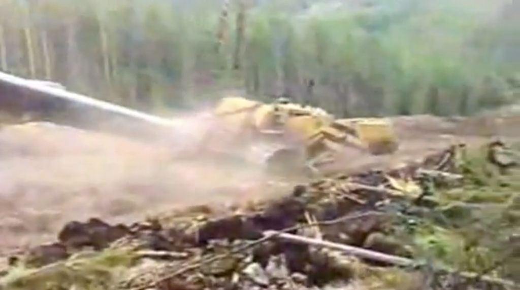 That blur of dust and yellow iron is a pipelayer that's decided to make its way down the mountain.
