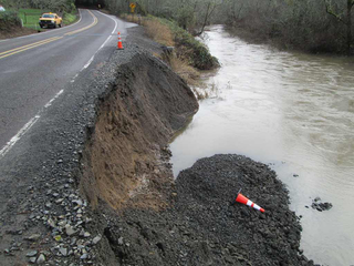 A portion of a road's shoulder collapses into a nearby river. (Photo: ODOT / Flickr)