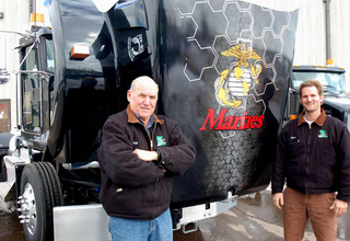 Valley Paving owner Rich Carron and his son, Brent Carron, stand beside the company's Kenworth T800 with the U.S. Marine Corps emblem.