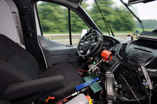 A robotic test driving system controls a Ford Transit van. The hardware is pictured here.