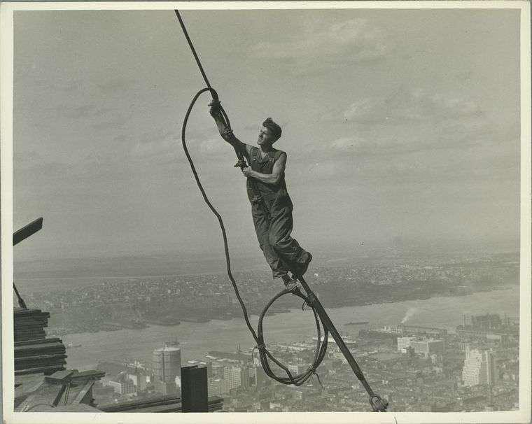Worker clings to a wire during construction of the Empire State Building. Credit: Lewis Wickes Hine