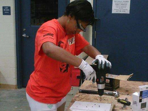 Shere Tolbert, 14, uses a drill at the Rosie's Girls construction camp in Cincinnati. Credit: WCPO.com