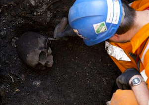An archaeologist uncovers a skull as construction continues on London's Crossrail commuter line. Credit: Alastair Grant/AP