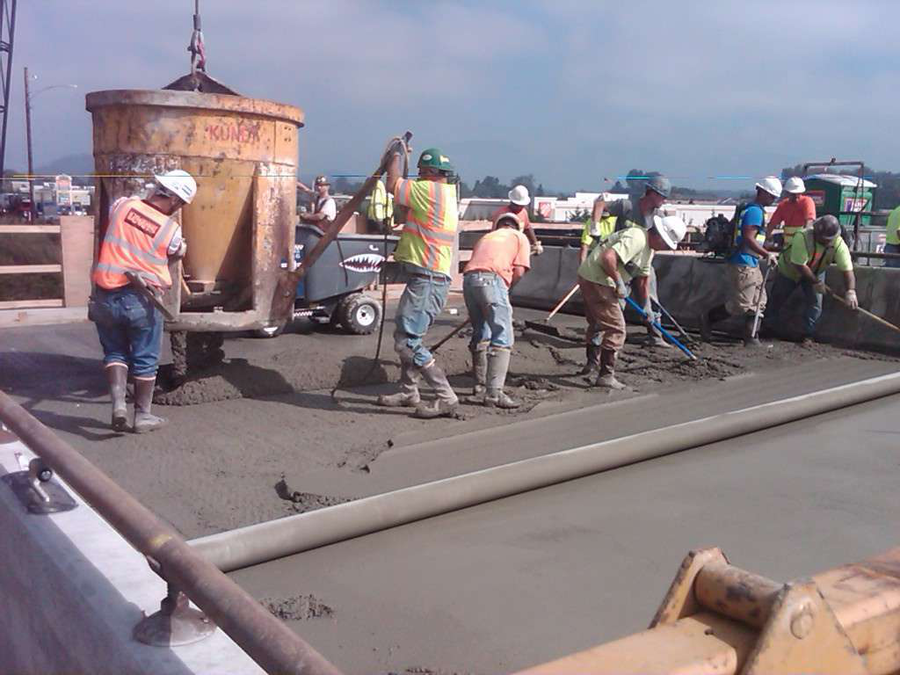 Crews smooth out concrete as a crane uses a bucket to pour the material. (Photo: WSDOT)