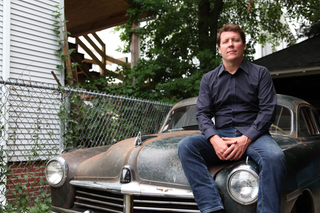 Dan McNichol sits on the 1949 Hudson he will drive during the tour.