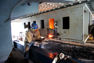 A man works on temporary bearings on shearkey. (Photo: Caltrans)