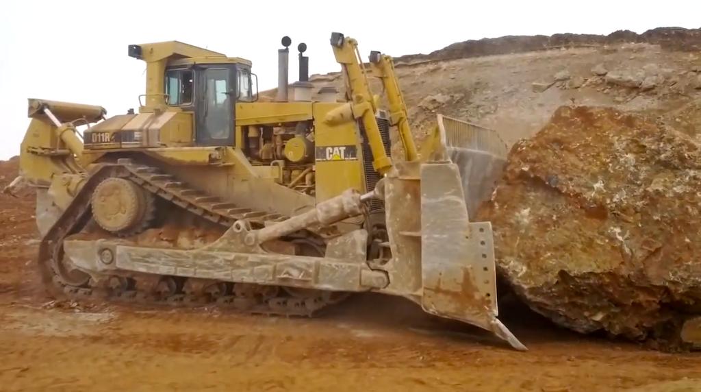 Caterpillar D11R pushing a rock