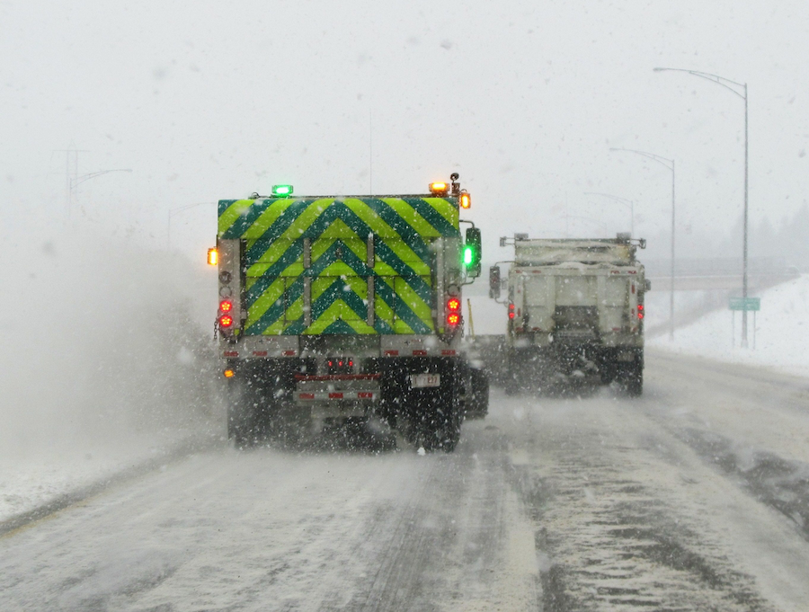 Plows push snow on to the shoulder of Interstate 77, resulting in a snow cloud several feet high.