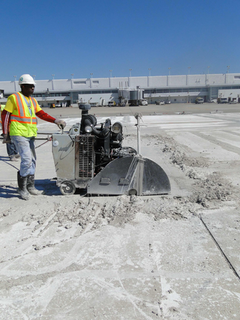 The slurry is swept to the edge of the perimeter of the work area, where it begins to solidify, while sawcutting continues.