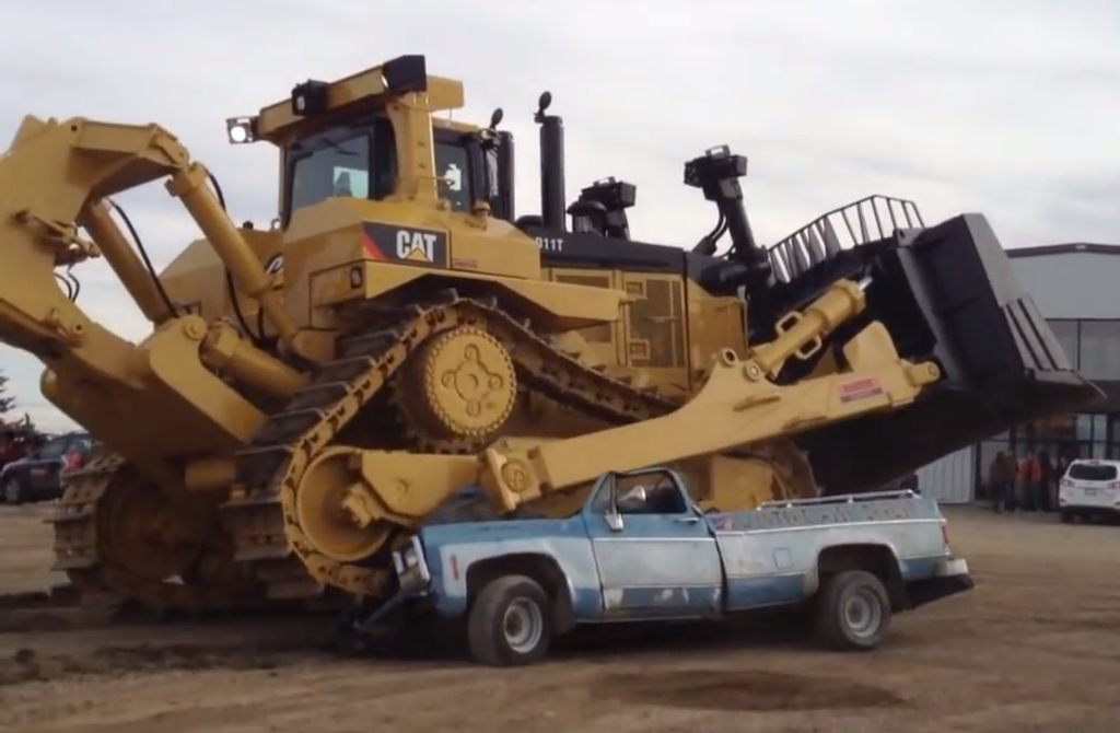 Cat D11T runs over old pickup truck