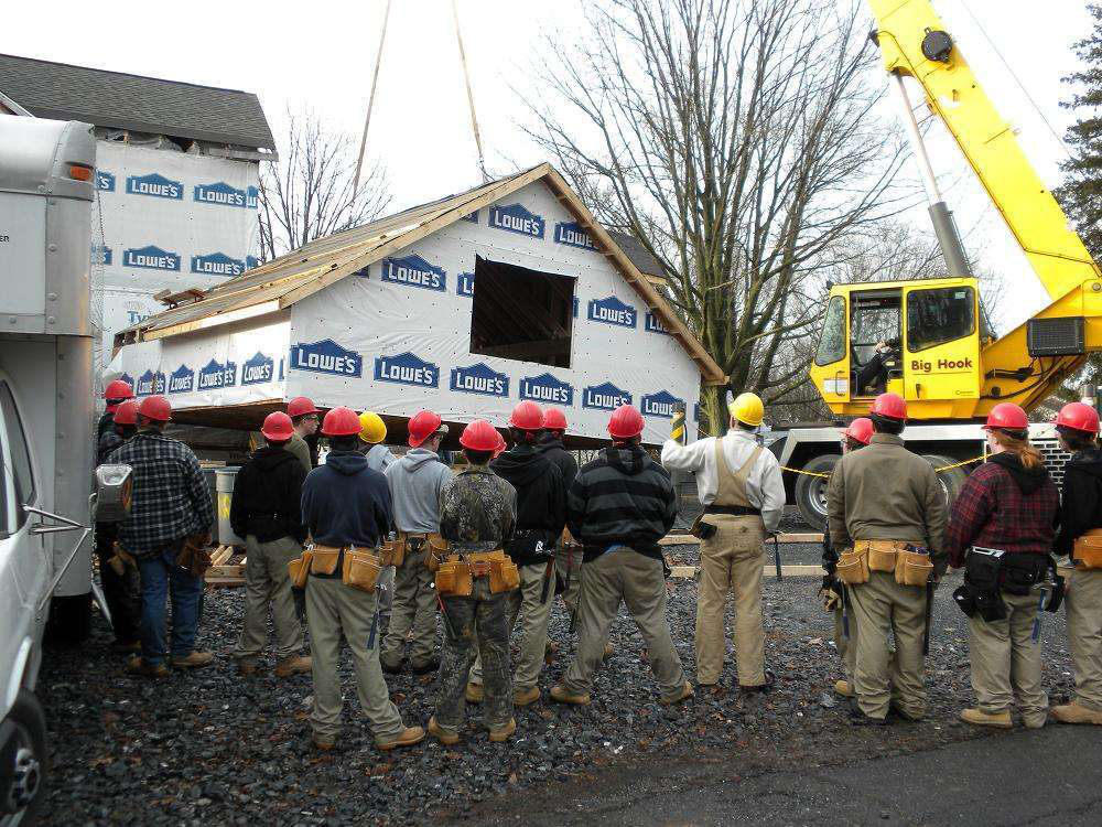 Students in the Fredrick County (Maryland) Career and Technology Center carpentry program observe a garage craning on the site of the program's annual project house.