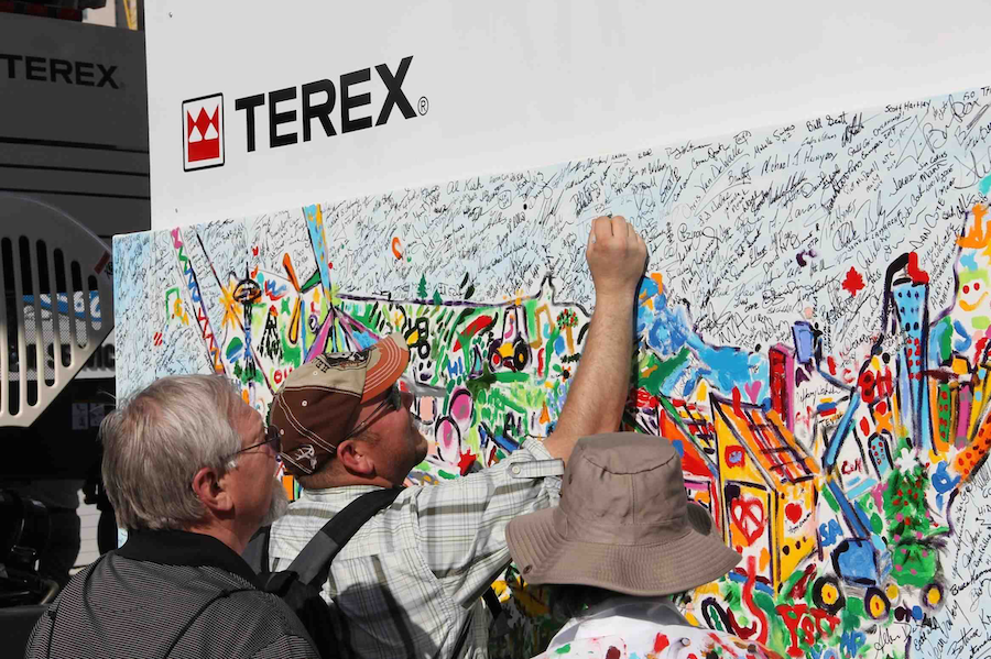 "ConExpo-Con/Agg 2014 attendees add their fingerprints and signatures to the ""I Make America"" painting. (Photo courtesy of Terex)"