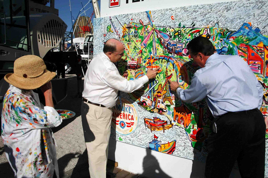 "Terex Chairman and CEO Ron DeFeo and AEM President Dennis Slater add their fingerprints to the ""I Make America"" painting. (Photo courtesy of Terex)"