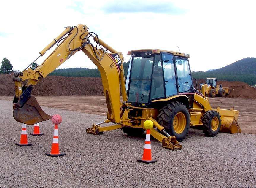 A patron at Big Toy Playground attempts to use a backhoe bucket to remove a basketball from a cone.