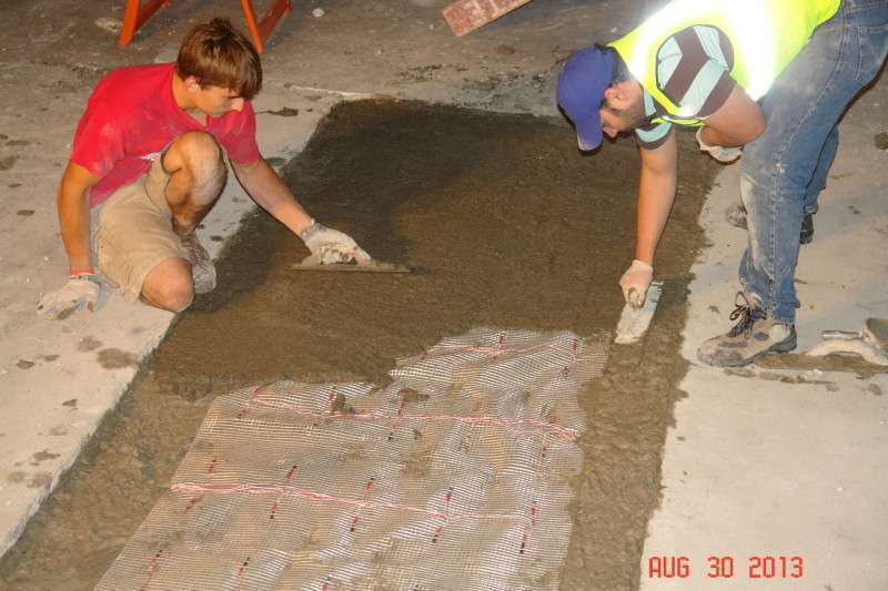 Students at the University of Wisconsin-Milwaukee install a slab of a new waterproof concrete atop data-gathering sensors.