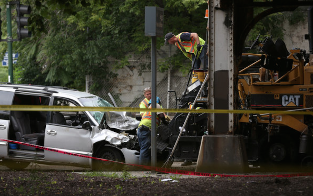 A crew works to dislodge a minivan from a paver after a crash in Chicago Saturday morning that killed one construction worker. Credit: Abel Uribe/Chicago Tribune