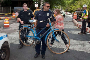 A New York City police officer carries away a woman's bike after she was hit by a cab.