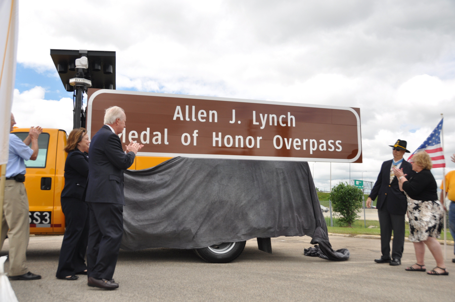 (from left to right) Illinois Tollway Executive Director Kristi Lafleur, State Sen. Terry Link, Allen J. Lynch and former State Rep. JoAnn Osmond applaud after overpass sign is unveiled.