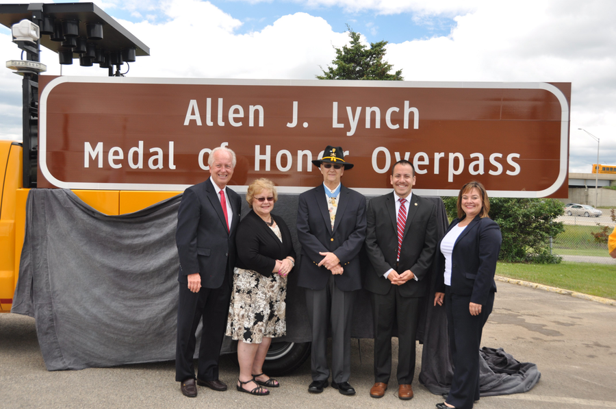 (left to right) State Sen. Terry Link, former State Rep. JoAnn Osmond, Allen J. Lynch, Illinois Department of Veterans' Affairs Assistant Director Rodrigo Garcia and Illinois Tollway Executive Director Kristi Lafleur stand in front of the new sign.