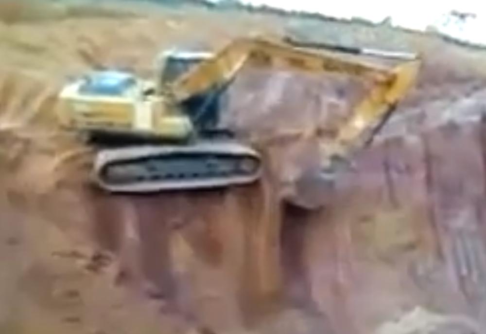 Excavator topples off bench