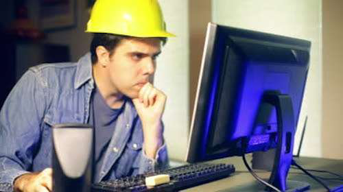 Construction worker looking at computer monitor