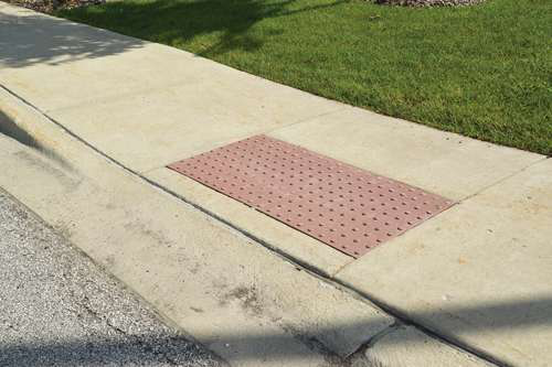 Pictured is a regulation curb on a suburban street. An important part of this requirement is the obligation that whenever street, roadways or highways are altered, curb ramps be provided where street level pedestrian walkways cross curbs.