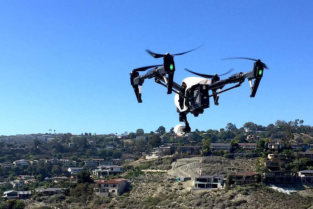 A drone on hire from the new DroneBase service, hovers during a residential job.
