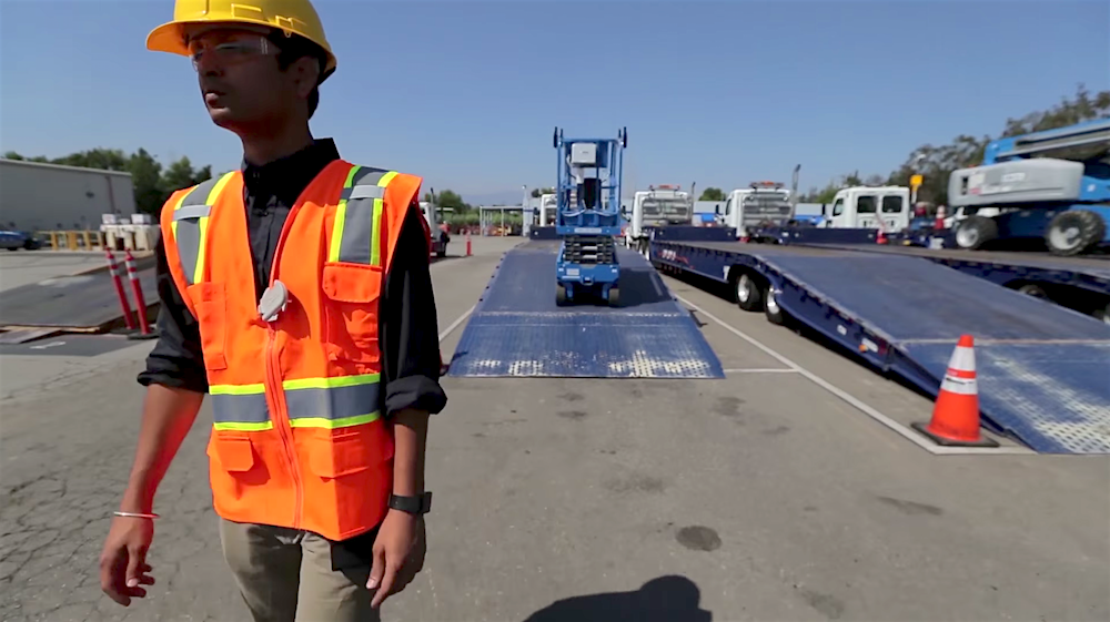 "A scissor lift follows a United Rentals employee off of a truck. 5D Robotics' ultra wide band (UWB) radio technology allows machines to ""see"" and respond to human instruction thanks to tags worn or carried by employees."