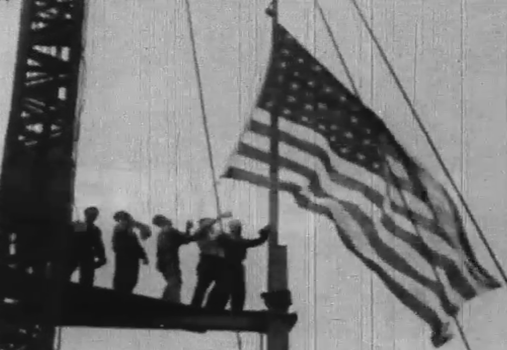 Workers raise the American flag during construction of the Empire State building.