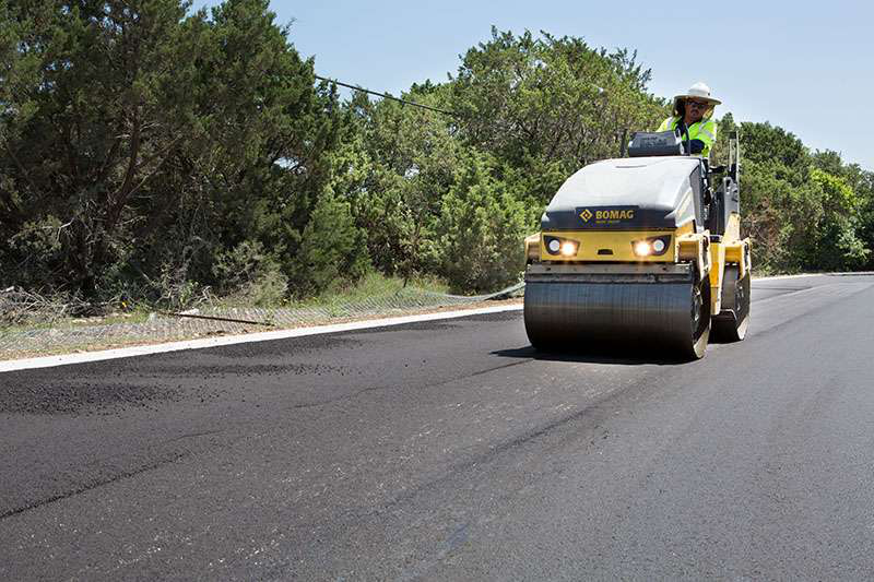 Crew member rolling asphalt