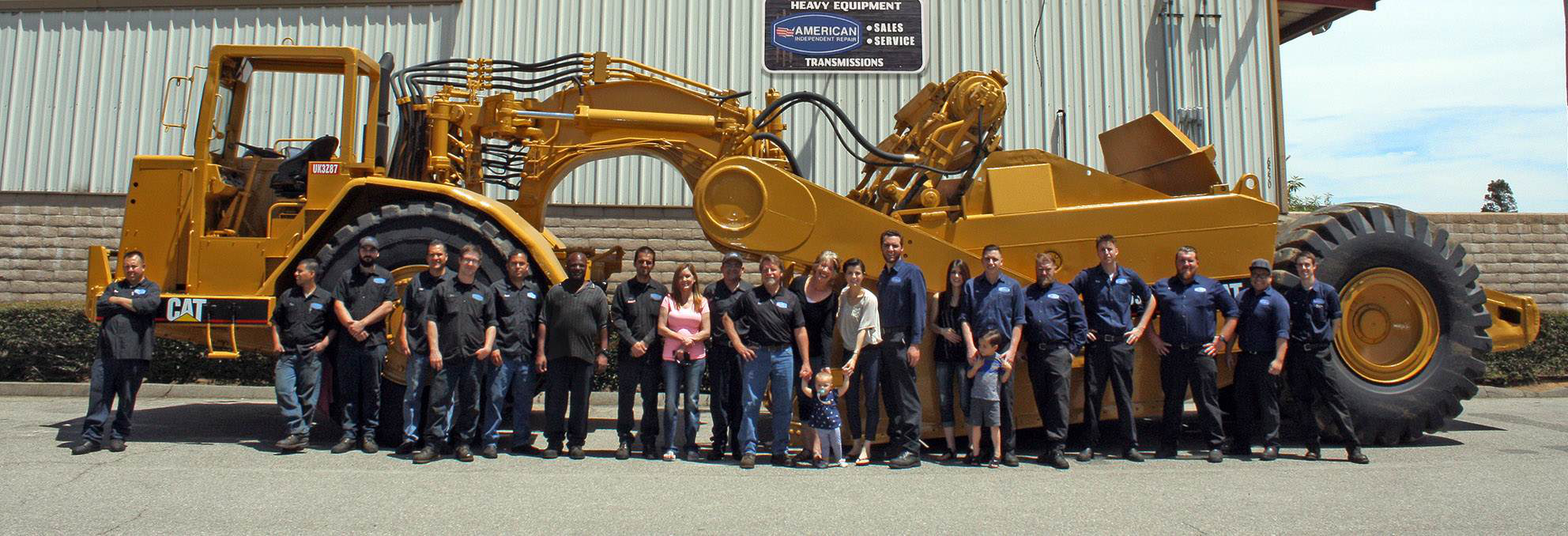 American Independent, Inc. crew standing in front of CAT charlotte nc dump trucks