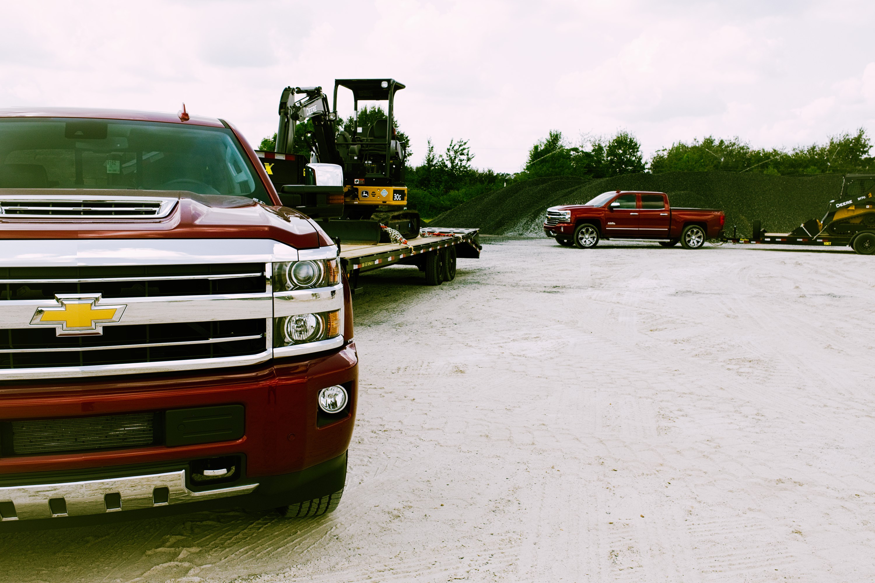 chevy silverados hailing trailers with john deere equipment