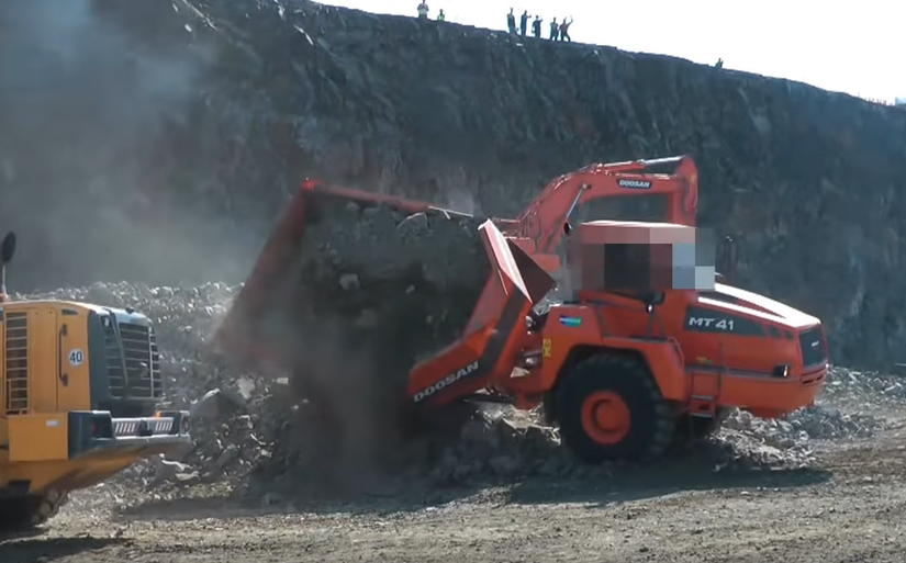 rock pile tips over articulated dump truck