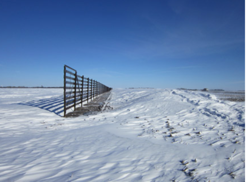 Fence standing in a field of snow