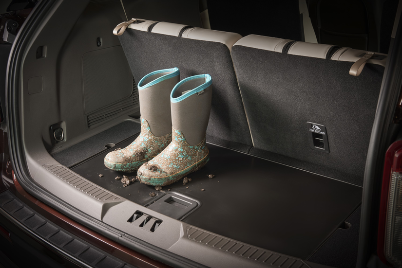 Mudboots sitting on reversible load floor in the rear of a new Ford Explorer