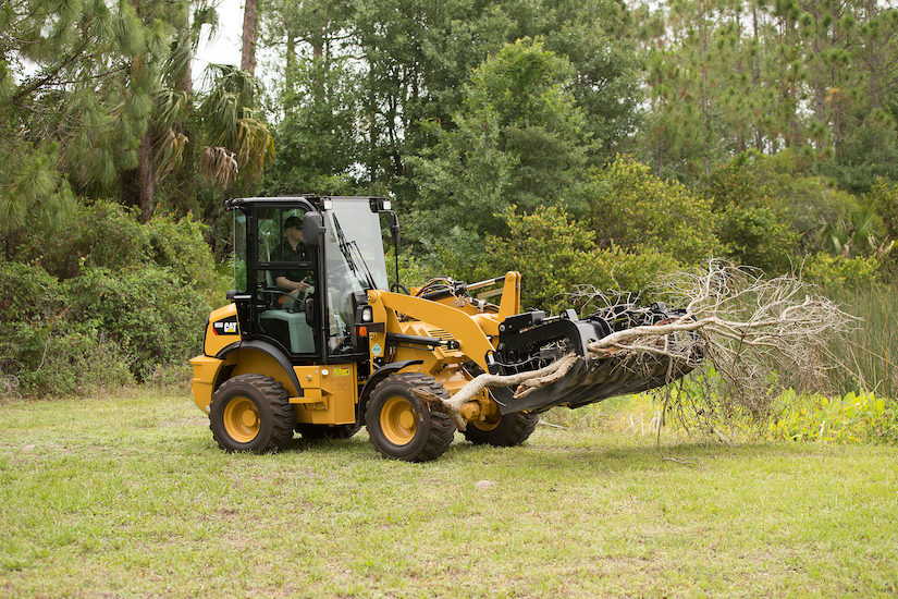 Caterpillar compact wheel loader with industrial grapple rake attachment