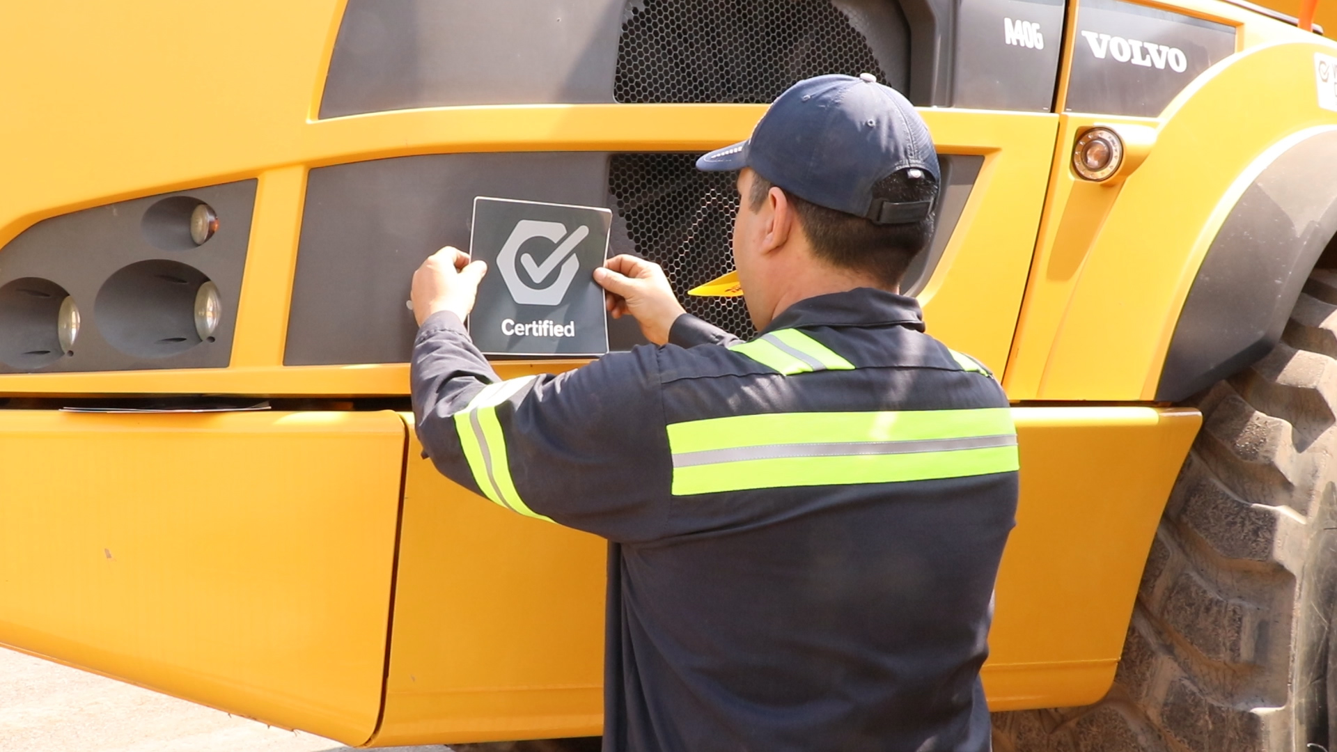 Certified sticker being placed on Volvo construction equipment