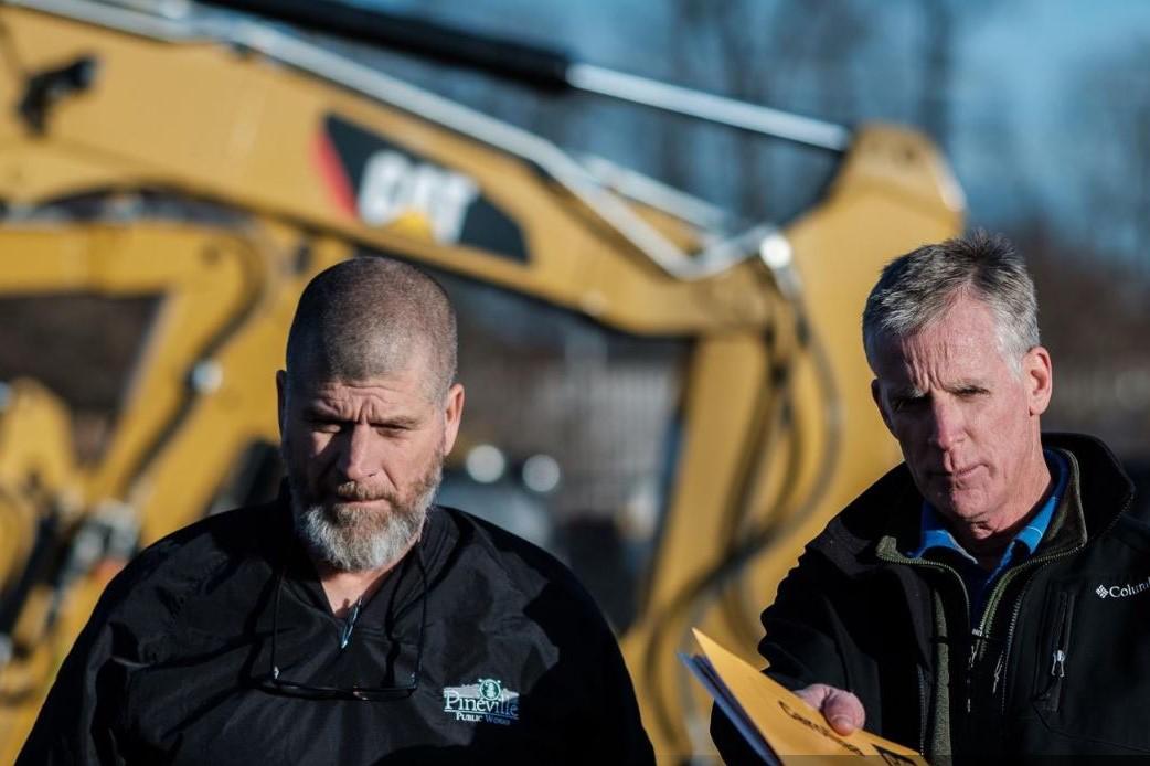 Two men in front of Caterpillar heavy duty equipment