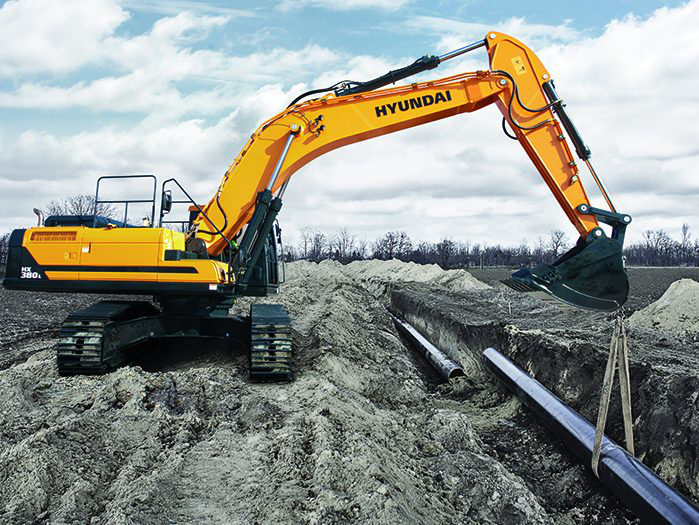 Hyundai excavator lowering a pipe into a trench