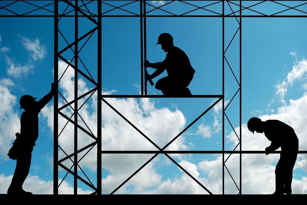 Silhouette of construction workers and metalwork against a blue sky with fluffy white clouds