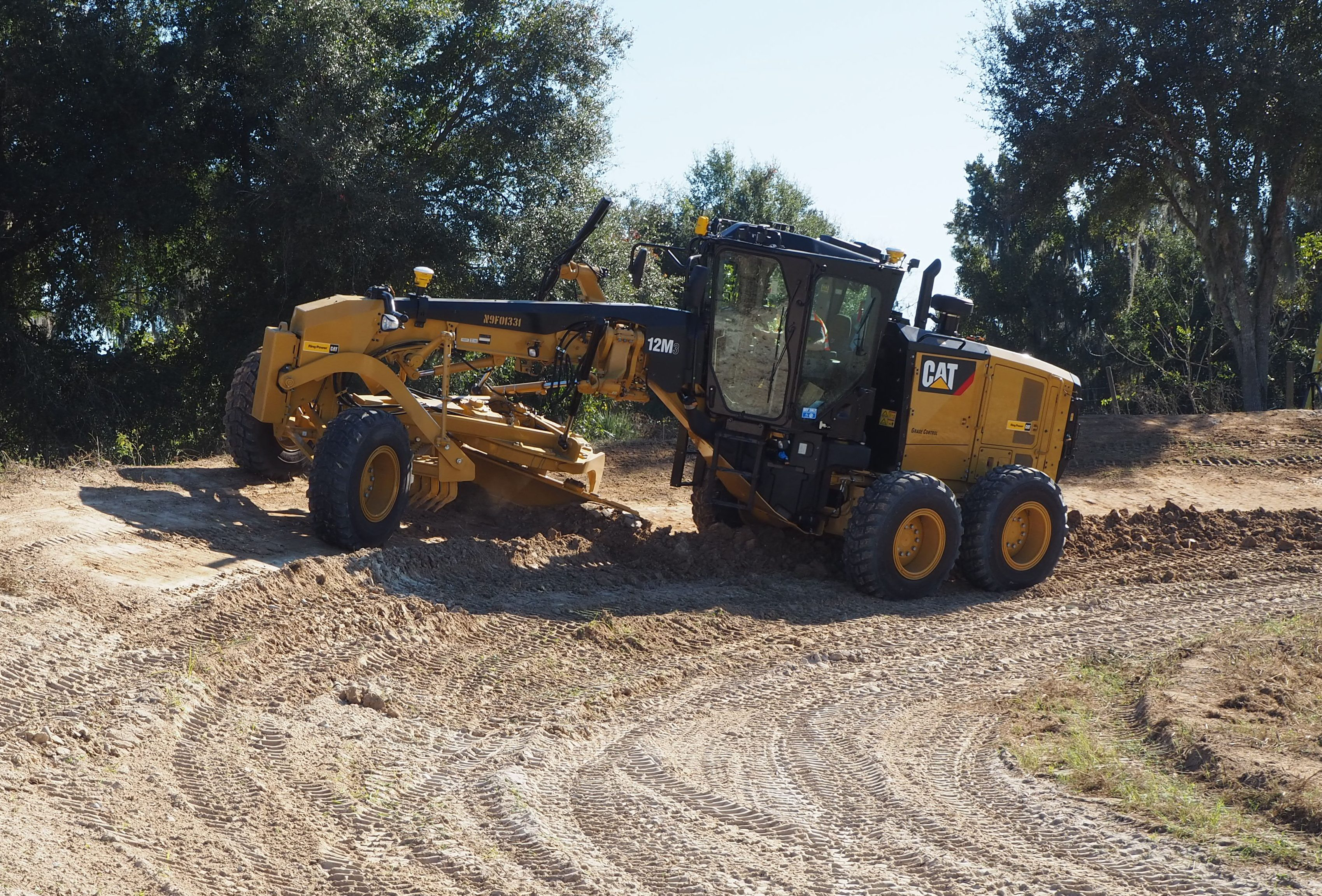A motor grader working on a slope with the Trimble mastless grade control