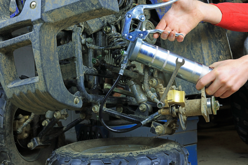 Hand-held grease gun being used to grease equipment parts