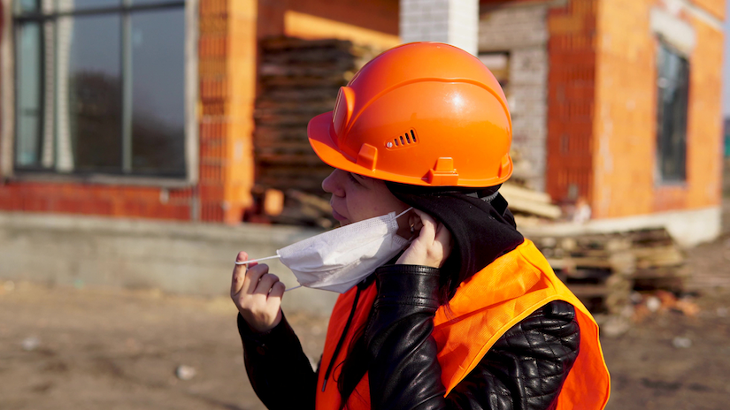 Construction worker in an orange vest and hard hat putting on a face mask